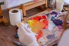 L'artista espelle pittura dai tubi sulla tavolozza per i colori mescolantesi t Immagine Stock Libera da Diritti
