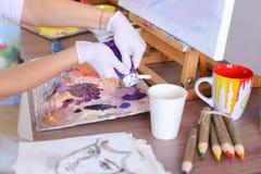 L'artista espelle pittura dai tubi sulla tavolozza per i colori mescolantesi t Immagine Stock