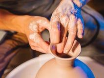 L'artista fa funzionare le mani, che delicatamente creando correttamente fatto a mano a forma di da argilla Terraglie tradizional immagine stock libera da diritti