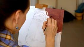 L'artista femminile dipinge il materiale illustrativo dell'immagine nello studio di arte Fotografia Stock