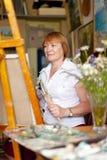 L'artista femminile dipinge una maschera su tela Fotografia Stock