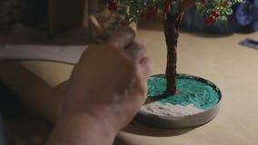 L'artista femminile sta dipingendo l'albero fatto a mano del cavo prima del processo della vernice stock footage