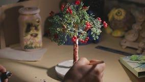 L'artista femminile sta dipingendo l'albero fatto a mano del cavo prima del processo della vernice archivi video