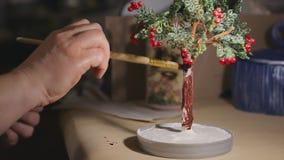 L'artista femminile sta dipingendo l'albero fatto a mano del cavo prima del processo della vernice video d archivio