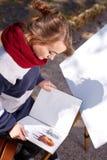 L'artista femminile sta dipingendo un'immagine nel parco di autunno Fotografia Stock