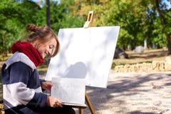 L'artista femminile sta dipingendo un'immagine nel parco di autunno Fotografie Stock