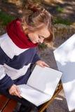 L'artista femminile sta dipingendo un'immagine nel parco di autunno Immagine Stock