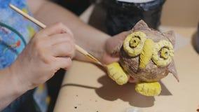 L'artista femminile sta pulendo il gufo fatto a mano prima del processo della vernice archivi video