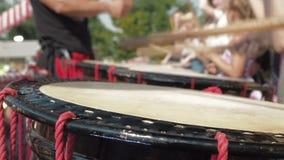 L'artista giapponese insegna ai bambini a giocare sui tamburi di taiko sulla scena durante il festival giapponese archivi video