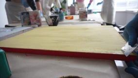 L'artista graffia la pittura con una spatola Vernici le latte Vernice gialla stock footage