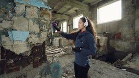 L'artista grazioso dei graffiti della giovane donna sta dipingendo con la pittura di spruzzo dentro il vecchio magazzino e sta as archivi video