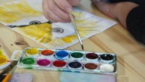 L'artista immerge una spazzola in pittura e disegna stock footage