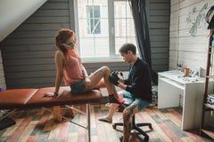 L'artista maschio del tatuaggio fa un tatuaggio su una gamba femminile Fotografia Stock