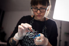 L'artista matrice del tatuaggio prepara gli strumenti per tatuare Immagine Stock