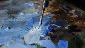 L'artista mescola le pitture ad olio con una spazzola sulla tavolozza stock footage