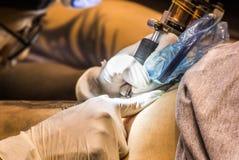 L'artista professionista del tatuaggio fa un tatuaggio Fotografia Stock