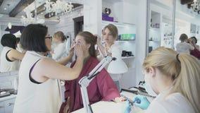 L'artista pulisce il fronte della donna ed il parrucchiere fa l'acconciatura dell'interno archivi video