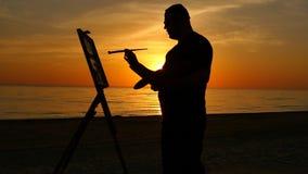 L'artista scrive una siluetta dell'immagine all'aperto al tramonto stock footage