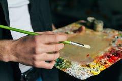 L'artista tiene una tavolozza con le pitture e una spazzola e sta andando dipingere su tela per mescolare le pitture ad olio Immagini Stock Libere da Diritti