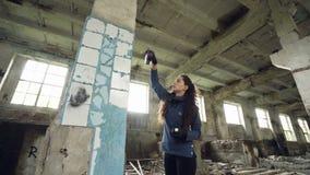 L'artista urbano della ragazza attraente sta dipingendo i graffiti in costruzione abbandonata con le pareti sporche e finestre, s stock footage