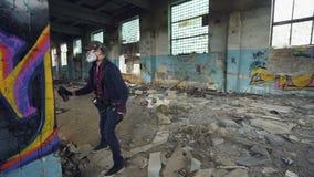 L'artista urbano della via sta decorando vecchio la casa abbandonata della colonna interno con le pareti sporche e finestre, sta  stock footage