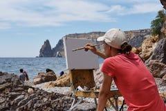 L'artiste avec un chevalet image stock