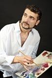 L'artiste créatif avec la palette et les brosses regarde vers Photographie stock libre de droits