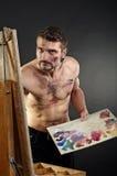 L'artiste créatif avec la palette et les brosses regarde vers Images stock