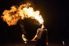 L'artiste d'exposition du feu respirent le feu dans l'obscurité photo stock