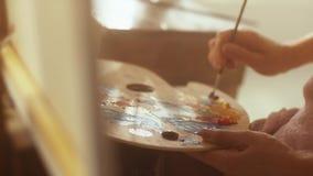 L'artiste de femme âgée par milieu s'assied dans le studio d'art tenant la palette de peintures à l'huile sur elle des recouvreme banque de vidéos