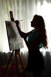L'artiste de femme de silhouette dessine la photo de peinture sur le chevalet Photos libres de droits