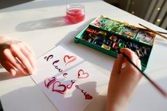 L'artiste de femme en italique écrit l'inscription italique sur le papier s Image stock