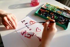 L'artiste de femme en italique écrit l'inscription italique sur le papier s Photo libre de droits