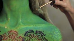 L'artiste de femme faisant l'art de visage d'aquagrim sur des glands de Halloween verdissent les fausses pierres fascinantes effr banque de vidéos
