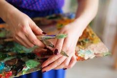 L'artiste de fille tenant une palette avec les peintures à l'huile, la brosse et le copain Image stock