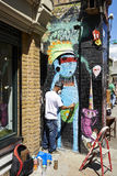 L'artiste de graffiti peint le mur sur la ruelle de brique Photos libres de droits