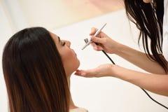 L'artiste de maquillage à l'aide du météorographe faisant un aerographe composent images stock
