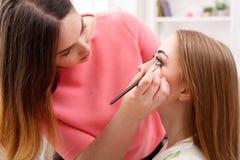 L'artiste de maquillage appliquent le fard à paupières avec la brosse, beauté Photographie stock