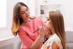 L'artiste de maquillage appliquent l'ombre de sourcil avec la brosse, beauté Image stock