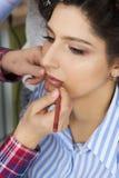 L'artiste de maquillage faisant un maquillage pour la jeune mariée photos libres de droits