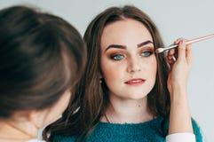L'artiste de maquillage fait le maquillage de la fille image libre de droits