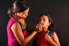 L'artiste de maquillage de femme fait le maquillage à une petite fille, Pune, maharashtra photo libre de droits