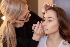 L'artiste de maquillage peint des sourcils avec la brosse images libres de droits