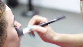 L'artiste de maquillage professionnel peint un modèle clips vidéos