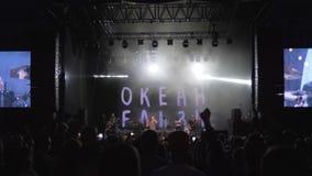 L'artiste de roche exécute sur l'étape devant la foule des fans au concert musical de nuit sur l'étape allumée avec de grands écr banque de vidéos