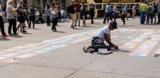 L'artiste de rue travaille aux drapeaux de l'affichage du monde sur le béton à Photo libre de droits