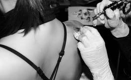 L'artiste de tatouage ombrage une plume sur le dos de la femme s Photos stock