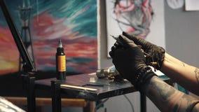 L'artiste de tatouage rassemble la machine de tatouage le maître de tatouage de fille prépare une mitrailleuse rotatoire de tatou banque de vidéos