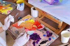 L'artiste expulse peinture des tubes sur la palette pour les couleurs de mélange t Images libres de droits