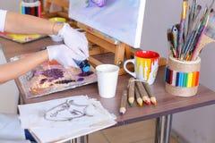 L'artiste expulse peinture des tubes sur la palette pour les couleurs de mélange t Photographie stock
